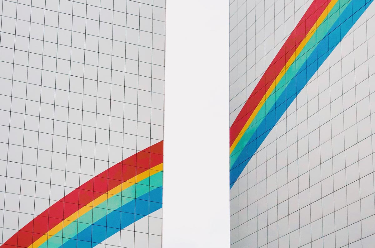 Two building façades with rainbow painted on.